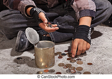 Beggar child counting coins sitting on damaged concrete...