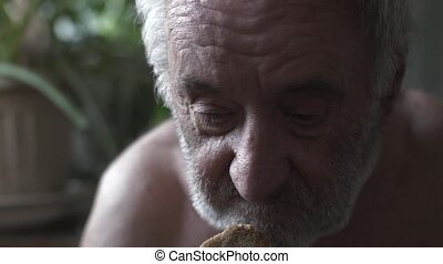 Beggar eating piece of bread - Poor old man eating piece of...