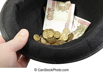 Beggar - Hand with hat filled with banknotes and coins