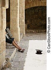 Beggar hidden accordion musician with hat on floor on Ibiza...