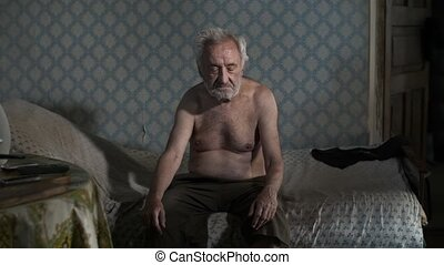 Beggar man sitting on a bed at old house
