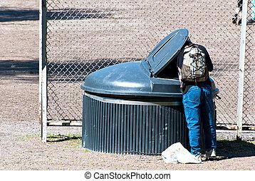 Beggar man. - The poor man seeks food in the garbage.
