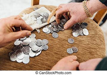 Beggar old man considers coins to buy food.