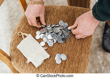 Beggar old man considers coins to buy food.