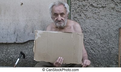Homeless old man with a piece of cardboard box asking for help