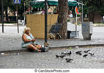 Beggar woman feeding pigeons in Rome