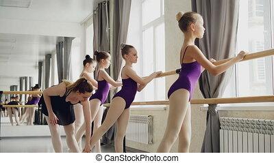 Beginning ballet dancers are lerning to raise leg backward...