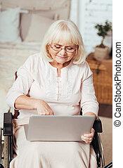 behaglig, äldre kvinna, användande laptop, in, den, rullstol
