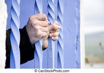 behind bars, person inside building holding bars on window
