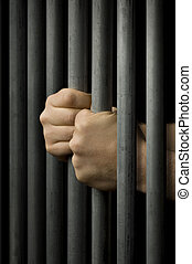 Behind Bars - Two hands clutching prison bars