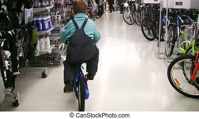 behind boy on bicycle in shop