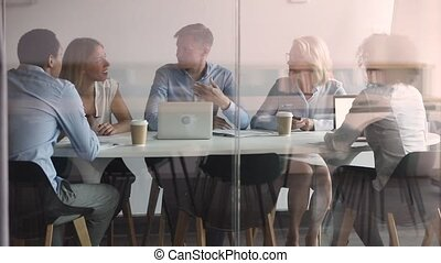 Behind closed glass doors multi-racial company staff and team leader gather on morning briefing sit in board room, representative making offer to client partners negotiating future cooperation concept