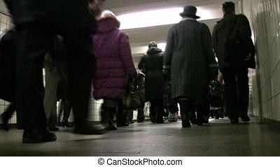 Behind crowd people going in subway corridor. Low view.