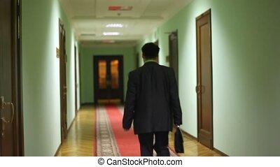 behind deputy assistant walking away along corridor and...