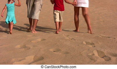 behind family of four on sand