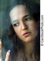 Behind glass - Woman with sad smile behind a wet window