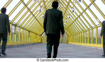 behind marching businessmen clones on bridge