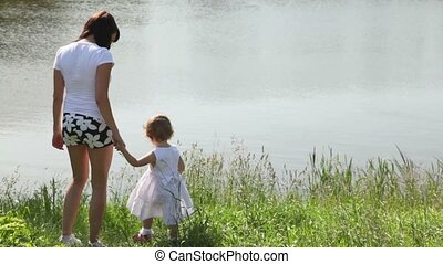 behind mother and her daughter are standing on bank of river and looking at it