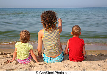 behind mother with children on beach