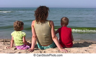 behind mother with children sit on beach