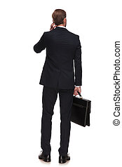 behind of pensive businessman holding suitcase and looking to side