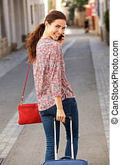 Behind of young female traveler walking on street with luggage and using mobile phone
