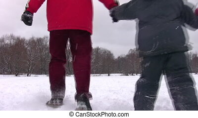 behind running family with son on winter pond - Behind...