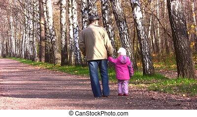 behind senior with little girl in autumn park