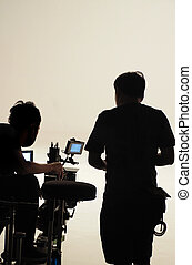 Behind the scenes of silhouette working people that making movie.