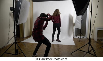 Behind the scenes photo shoot session of a blonde curly slim...