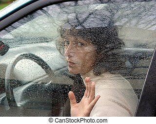 Behind the wheel - A woman in a car behind the wheel. Window...