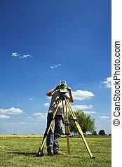 Behind Theodolite - land surveying in rural area.