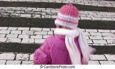 behind walking little girl on zebra crossing