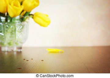 Beige background with blurred bouquet of vivid yellow tulip flowers. Focus on foreground