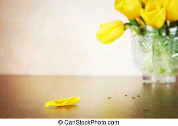 Beige background with blurred bouquet of yellow tulip flowers. Focus on foreground
