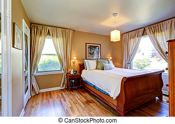 Beige bedroom with carved wood bed