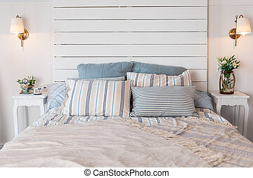 Beige blanket on king-size bed and cacti in gold pots on cupboard in spacious bedroom. King-size bed with soft bedhead and pastel pink bedding. Pastel blanket on bed in bedroom interior