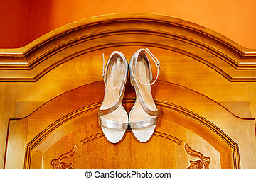Beige bride's sandals with mother-of-pearl on the texture of a wooden door.