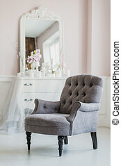 beige color upholstered chair in living room with flowers.