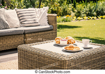 Beige color wicker table and settee on a porch during sunny afternoon in the garden. Croissants and coffee served on the table.