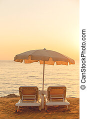 Beige cotton beach umbrella with two sunbeds by the sea