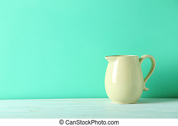 Beige jug on a green wooden table