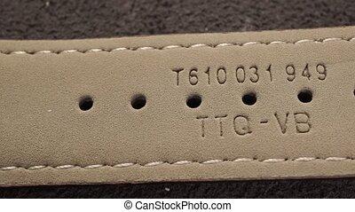 Beige leather watch wristlet. Inner side macro dolly shot...