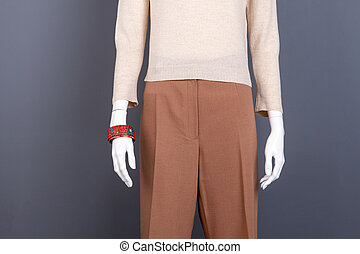 Beige sweater and brown trousers on mannequin.