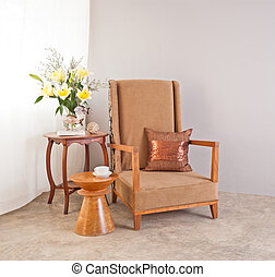 Beige upholstered chair in interior setting and coffee cup