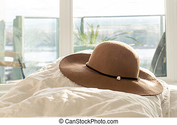 Beige woman's round sun hat with floral trim and wide brim, on a fluffy comforter in a bedroom, with balcony in the background. Depicting holidays, relaxation, lifestyle and fashion style.