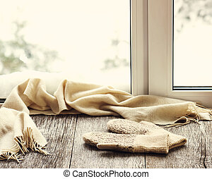 Beige woolen scarf and mittens located on wooden window...