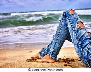 beine, von, frau sitzen, auf, kueste, bei, wasserlandschaft, mit, waves., heißer hund, bein, selfie.