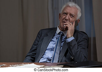 Being on the phone - Image of senior businessman being on...