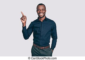 bekijken, this!, mooi, jonge, afrikaanse man, benadrukkend, en, het glimlachen, om te, u, terwijl, staand, tegen, grijze , achtergrond